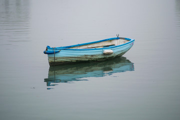 Small boat on clam water with reflection and mist.