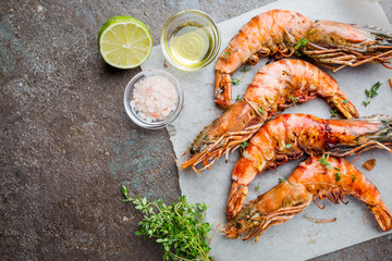 Grilled giant tiger prawns on paper with lemon and spices on vintage dark background, top view, copy space. Seafood dinner.
