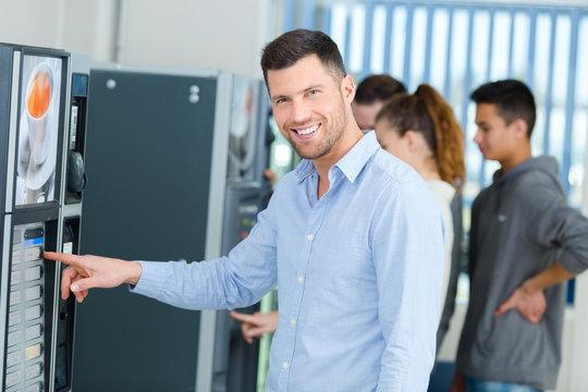 man posing while pressing vending machine