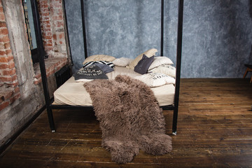Bed with a fur blanket in a photo studio on a wooden floor.