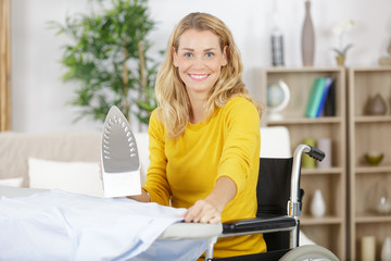 woman in wheelchair during ironing at home