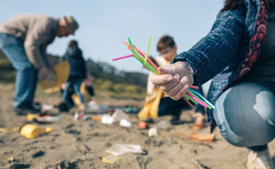 Woman hand showing handful of straws collected on the beach with group of volunteers working in the background. Selective focus in straws in foreground