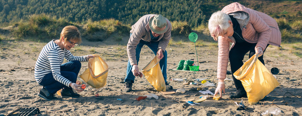 Group of senior volunteers picking up trash on the beach