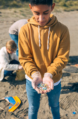 Young man showing microplastics collected on the beach