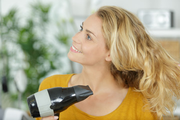 woman using hairdryer in the home
