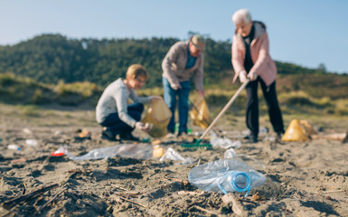 Group of senior volunteers picking up trash on the beach. Selective focus on plastic bottle in foreground