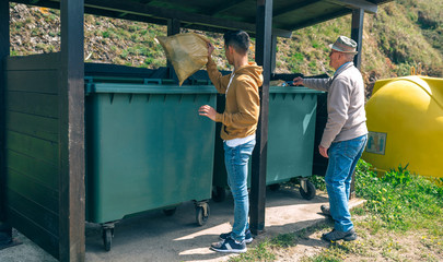 Senior man and young man throwing garbage to container