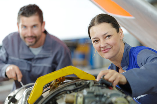 portrait of male and female aircraft mechanics at work