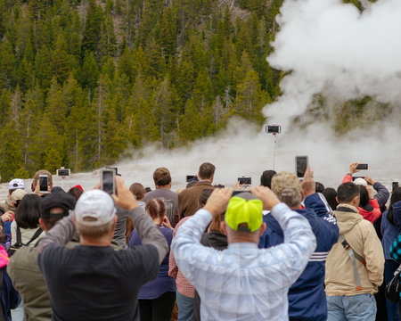A Crowd is Ready to Take Photos as Old Faithful Geyser Erupts in Yellowstone National Park