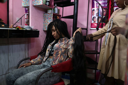 Woman has her hair extensions made in the Glamour hair salon in downtown Sao Paulo