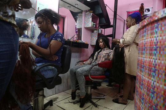 Women have their hair extensions made in the Glamour hair salon in downtown Sao Paulo