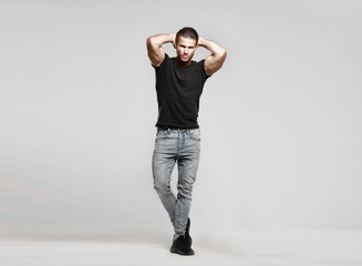 Muscular model sports young man in jeans and black t-shirt on a grey background. Fashion portrait of brutal sporty healthy strong muscle guy with a modern trendy hairstyle. Wall mural