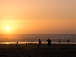 Silhouette of people at the Oregon coast during sunset