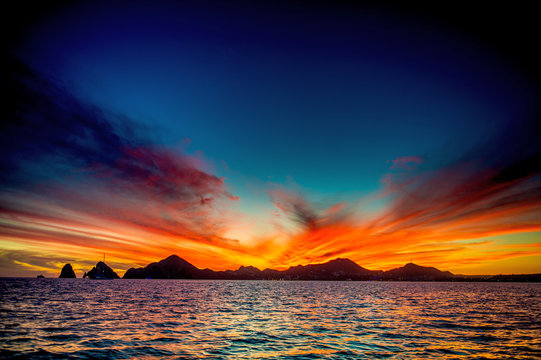 Beautiful Sunset of Seascape with Mountains silhouets. Sea off the Coast of Cabo San Lucas. Gulf of California (also known as the Sea of Cortez, Sea of Cortes. Mexico. Sunset over Cabo San Lucas