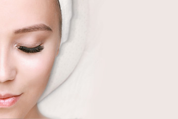 Eyelash extension procedure. Beautiful woman with long eyelashes and perfect glow clean skin. Girl in beauty salon getting facial treatment. Perfect trendy eyebrows. Fotoväggar