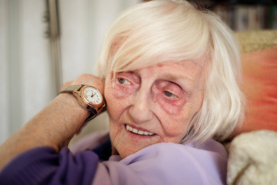 Blind old woman listens to the time on her speaking wrist watch.