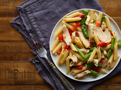 chicken penne pasta with red bell peppers and asparagus top down photo