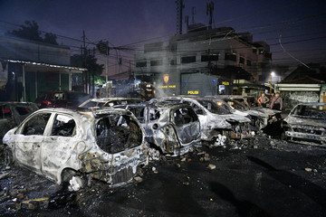 Police officers inspect the damage after cars were set on fire at Brimon (Mobile Police) Dormitory Complex, Petamburan, Jakarta
