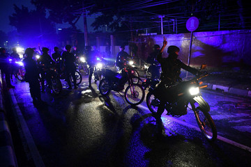 Police officers go on patrol outside the Brimon (Mobile Police) Dormitory Complex, Petamburan