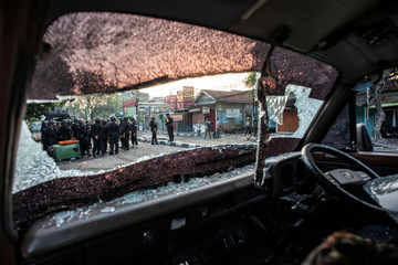 Police are seen through a broken windscreen of a car after early morning clashes with protesters in Jakarta