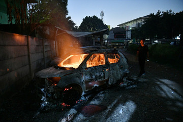 A man looks at a car that was set on fire by protesters at Brimob (Mobile Police) Dormitory Complex, Jakarta
