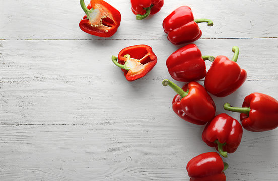 Ripe red peppers on white wooden background