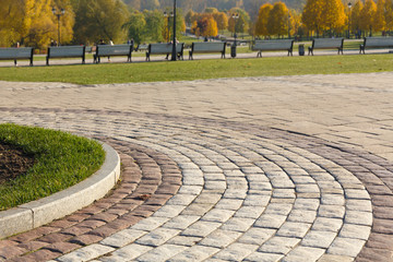 Curved path in the shape of a wave on the grass in the Park. Paved with tiles of different shapes. Wall mural