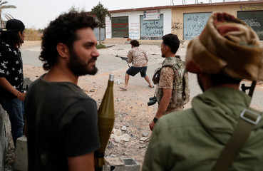 A fighter loyal to Libya's U.N.-backed government (GNA) fires a weapon during a clash with forces loyal to Khalifa Haftar at the outskirts of Tripoli