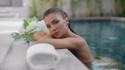 Young beautiful girl relaxes in the pool during spa procedures