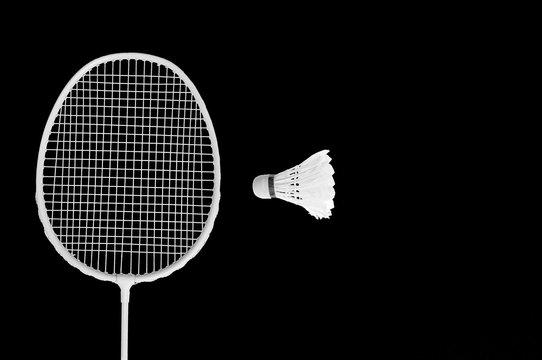 White badminton racket and shuttlecock isolated on black background