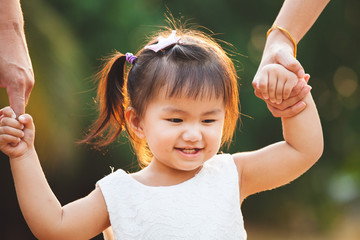 Cute asian little girl holding hand and walking with her parents in the park with love and happiness