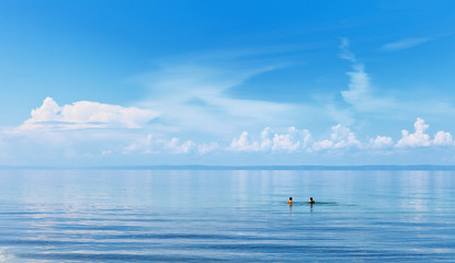 Lake Baikal on summer day. Two girls swimming in the blue water of the lake. White clouds are beautifully reflected in the water. Natural background. The concept of outdoor recreation, tourism, travel