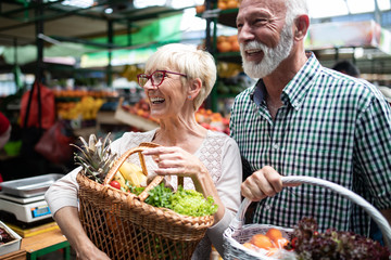 Shopping, food, sale, consumerism and people concept - happy senior couple buying fresh food