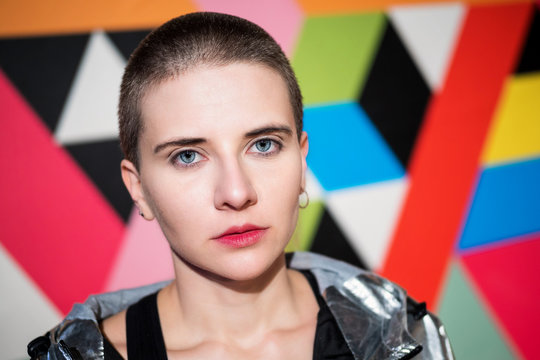 Portrait of young beautiful woman with short hair in a silver jacket on colourful geometric background