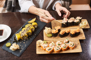 Four course lunch on special offer in luxury oriental restaurant. Elegant girl wrapped in blanket tasty delicious sushi set with seafood. Woman in white blouse eating Japanese dish using food sticks.
