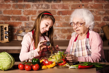 Little grandchild girl helps her granny to cook salad at kitchen