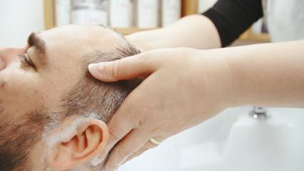 Applying shampoo on male head in sink