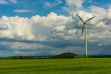 single wind turbine in rural area in front of storm cloud cumulus sky