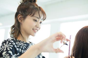 女性の髪の毛を切る女性美容師