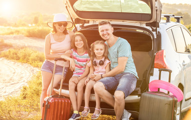 Happy pleasured family sitting on a trunk of a car with suitcases on a travel vacation