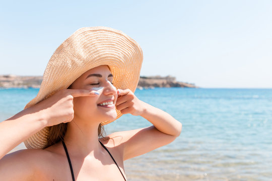 Pretty woman protects her skin on face with sunblock at the beach