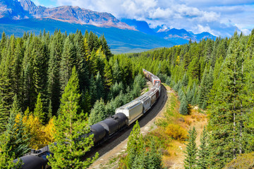 Long freight train moving along Bow river in Canadian Rockies ,Banff National Park, Canadian Rockies,Canada.  Fototapete
