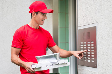 Pizza delivery man carrying boxes using the intercom