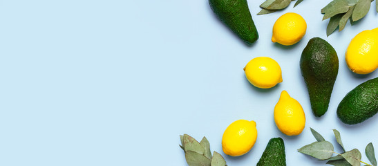 Ripe fresh avocado, fresh citrus lemons, eucalyptus twigs on pastel blue background top view Flat...