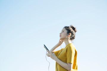 青空の下音楽を聴く20代女性