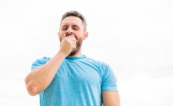 coach in fitness gym. after workout. man athlete in blue sport tshirt. sportswear fashion. yawning muscular male with beard. sleepy man isolated on white. sportsman with athletic body. early morning
