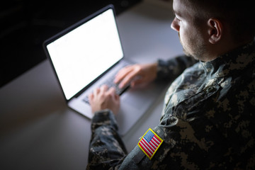 White caucasian soldier in USA military uniform working on the computer at night.