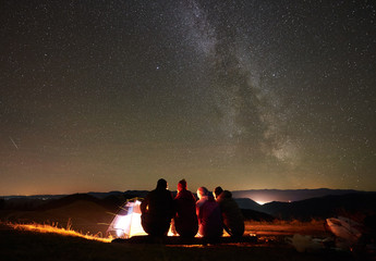 Night summer camping in mountains. Back view group of four hikers sitting on a bench made of logs together around bonfire near glowing tourist tent under night starry sky full of stars and Milky way.