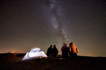Back view group of four friends tourists sitting on a bench made of logs together around campfire beside camp and tourist tent in the mountains under night starry sky full of stars and Milky way.