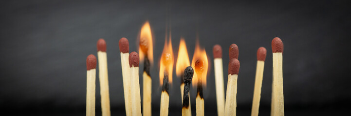 A group of matches, some of which are burning, banner